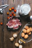 An arrangement of ingredients for tomato quiche with ham and mushrooms