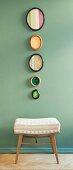 Biedermeier-Stoffmuster in ovalen Bilderrahmen über Polsterhocker an pastellgrüner Wand