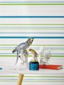 Grün-blau gestreifte Vliestapete, davor Beistelltisch mit Vogelfiguren