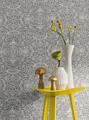 Gelber Metalltisch mit Vasen vor Vliestapete mit floralem Muster in Grautönen