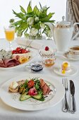 A breakfast table with prosciutto, mixed leaves, balsamic vinegar, bread and butter, cucumber, radishes, a soft boiled egg and a cheese plate