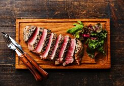 Grilled Tuna steak in sesame and Green salad on wooden board