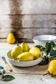 Fresh pears in a bowl on a wooden table