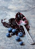 Blueberry jam with a spoon and fresh blueberries