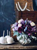 Blumenstrauss in silberner Vase auf rustikalem Holztisch