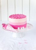 Pink-coloured ombre cake with sugar flowers for a child's first day at school