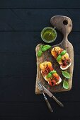 Fresh homemade toasts with mozarella, cherry tomatoes and basil served with pesto sauce