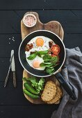 Pan of fried eggs, bacon, cherry tomatoes and fresh herbs with bread on wooden board over dark wooden background