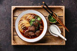 Asian noodles in broth with slow cooked Beef in wooden tray on dark background