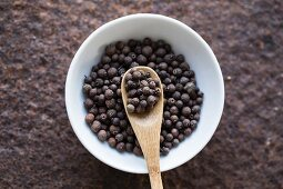 Allspice with a wooden spoon in a bowl (seen from above)