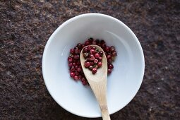 Red peppercorns with a wooden spoon in a bowl (seen from above)