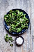Kale crisps with coarse salt on a plate