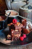Brownies mit Pekannüssen, Schokoladensauce und Himbeeren
