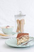 A slice of tiramisu cake and a cappuccino