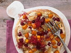 A pizza with beetroot and pumpkin