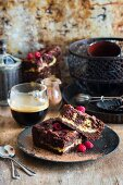 Two slices of chocolate and raspberry brownie cheesecake on a black plate