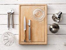 Bar utensils: a cocktail shaker, measuring jug, citrus press and garlic press