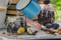 Plums being preserved in glass jars