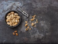 Whole almonds, a nutcracker, nutshells and almond seeds
