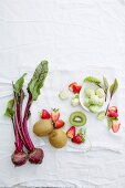 Beetroot, kiwi, strawberries, and brussels sprouts on a white background