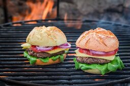Two homemade hamburgers on a barbecue with fire