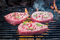 Fresh steaks seasoned with pepper and rosemary on a grill rack with fire