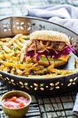 A burger with pulled pork, Cheddar, avocado cream and celeriac chips