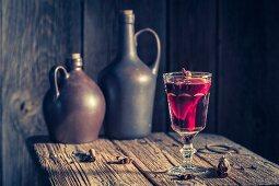 Ein Glas Glühwein mit Gewürzen auf rustikalem Holztisch zu Weihnachten