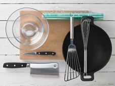 A wok with assorted kitchen utensils