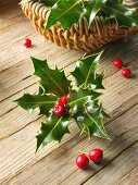Holly leaves with red berries in a basket on a wooden surface