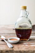 An arrangement of maple syrup in a bottle, in a dish and on a spoon