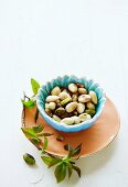 Roasted almonds and pistachios in a small bowl