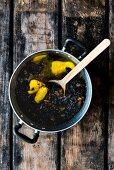 Trockenfrüchte und zerlassene Butter für Dinkel-Amaretto-Früchtekuchen im Kochtopf