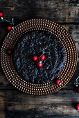 Spelt and amaretto fruit cake decorated with festive baubles (seen from above)