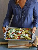 A woman holding a tray of baked feta and vegtables
