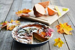 A sweet potato autumn cake decorated with autumn leaves, with a fresh sweet potato in the background