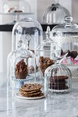 Vegan cookies and cupcakes under glass domes in a café