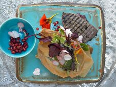 Algerian-style tuna fillets with puff pastry, pomegranates and a flower salad