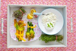 An arrangement of courgette flowers, fresh herbs and ricotta on a tray