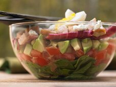 Colorful layered salad with spinach, bacon, chicken and avocado