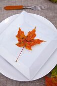 Fall diner celebration in the country, place card made out leaf on a white plate