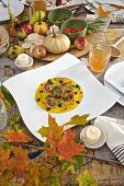 Seared scallops in saffron sauce with truffles, in white plate on country table with pumpkins apples and fall leaves