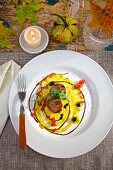 Seared scallops in saffron sauce with truffles on white plates on country table, with a candle and fall decorations
