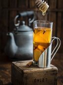 Cup of hot winter spiced tea with honey on a rustic background