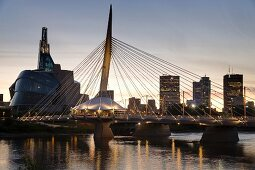 The Red River and the Esplanade Bridge with the Canadian Museum for Human Rights on the left and the skyline of Winnipeg, Province of Manitoba, Canada