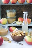 Apples, apple sauce, and apple juice on a shelf, with a bowl of Kaiserschmarrn (shredded sugared pancakes)