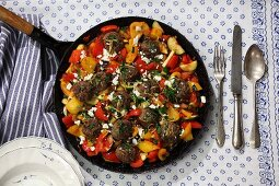 Vegetables in a pan with lemon meatballs