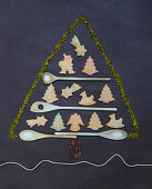 Gingerbread biscuits and wooden spoons in the shape of a Christmas tree