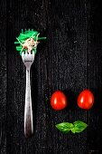 Italian pasta with tomato and basil on fork On wooden board