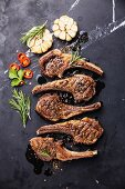 Roasted lamb ribs with spices and garlic on black marble background